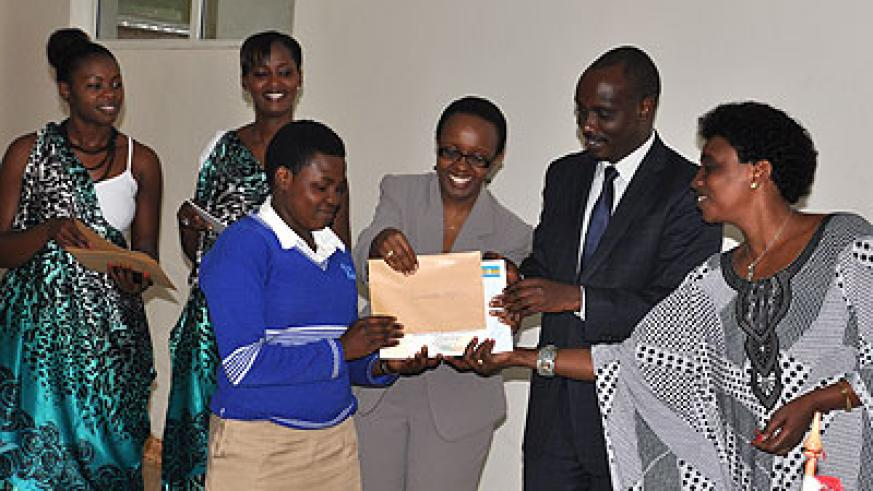 Muhongayire (R), Dr Sezibera and Haba hand a certificate to one of the winners, Delphine Uwamahoro, from Nyarutovu in Burera District. Athan Tashobya