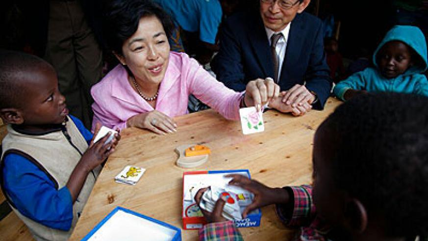 Japanese envoy Kazuga Ogawa and his wife play with children after the inauguration of the centre.  Collins Mwai.