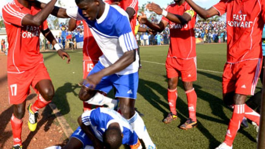 Rayon Sports' defender Abouba Sibomana pushed away André Lomami (L) after the Espoir striker appeared to have struck Rayon skipper Ndayisenga (on the floor) during a heated exch....