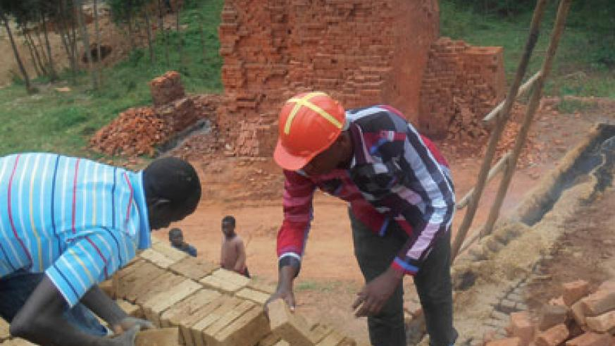 Francois (right) helps one of his workers prepare bricks for burning. The New Times / Peterson Tumwebaze.