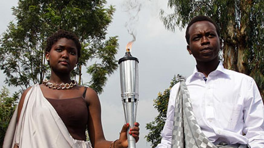 Pascaline Niyigena (L) and Adolphe Gahima carry the Kwibuka Flame from Kigali Genocide Memorial Centre in Gisozi on January 7 shortly after the lighting ceremony. (File)