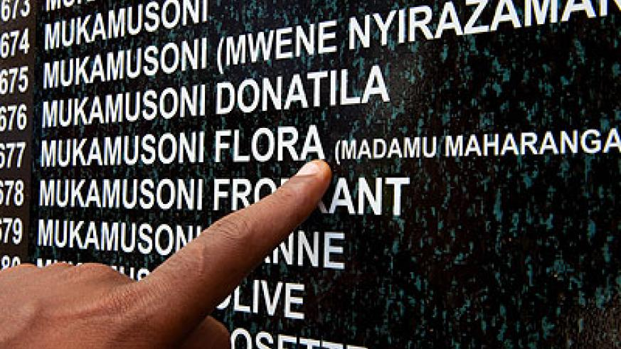 A survivor points at a name on the memoriam wall at Rebero Genocide memorial site yesterday.