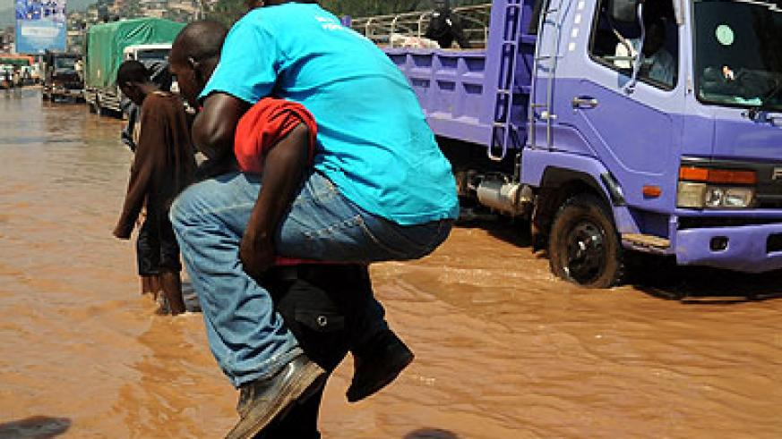 A man is carried across the flooded Nyabugogo highway after paying Rwf100.  File.