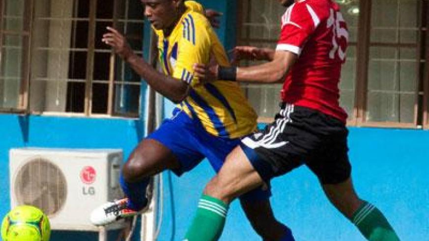 Striker Elias Uzamukunda seen against a Libya defender in March last year. He will lead an offensive for Amavubi as they seek a bright start to the 2015 Africa Nations Cup qualifie....