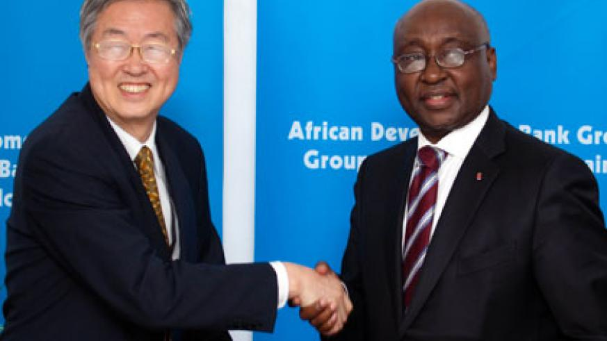 Dr. Zhou Xiaochuan (L), Governor People's Bank of China, shakes hands with AfDB President Dr. Donald Kaberuka after the signing ceremony. (Timothy Kisambira)