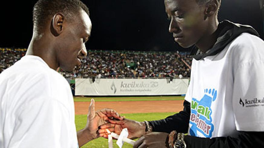 Two boys light candles during the 20th commemoration of the Genocide against Tutsi. Youth today have pledged to sustain a unified Rwanda. File.