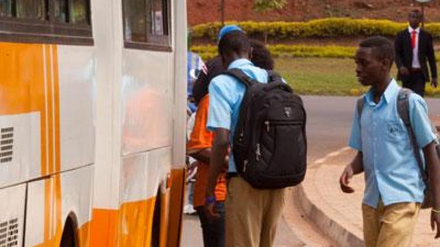 Students wait for their tickets before boarding  a bus to school. (Timothy Kisambira)