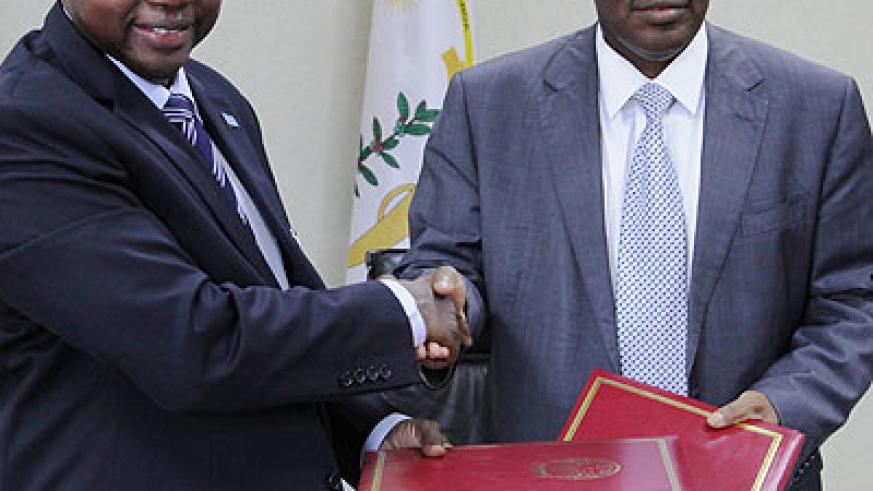 UN resident coordinator Lamin Manneh (L) and Finance Minister Claver Gatete pose for cameras after signing a Rwf19 billion financial support on Tuesday. John Mbanda.