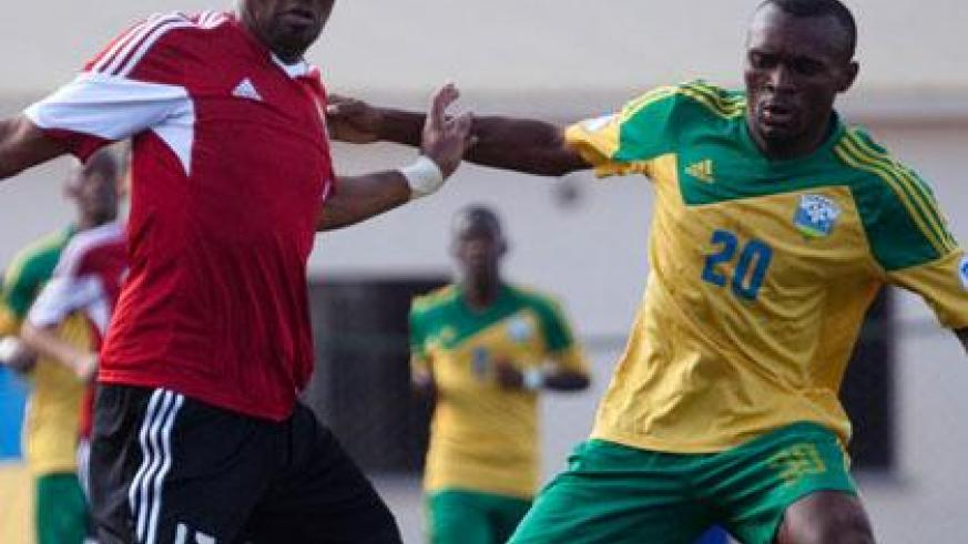 Striker Jacques Tuyisenge (R) seen against a defender from Libya in a past qualifying match scored the lone goal against Gabon in yesterday's friendly match held at Kigali Regional....