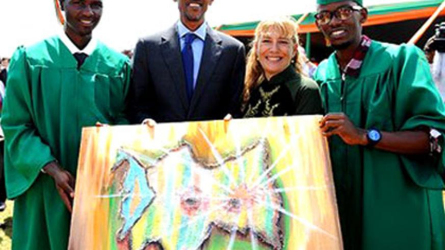 Nkunda (L) presents a painting to President Kagame during his graduation. The youth, who only learnt to speak English five years ago, has shaken off a yoke of misery to realise his dreams, mainly through his passion–art. Courtesy.