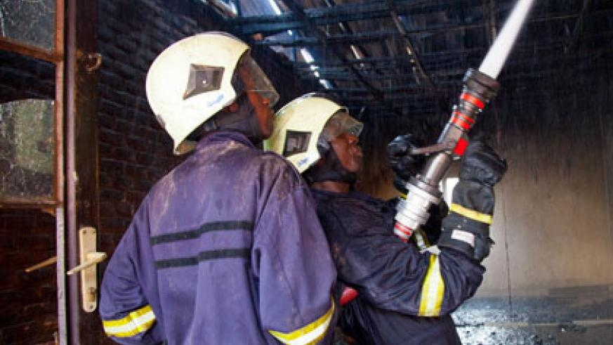 Police fire fighters struggle to put out the fire. Timothy Kisambira.