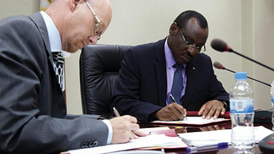 Molander (left) and Gatete sign the funding deal last week.  T. Kisambira