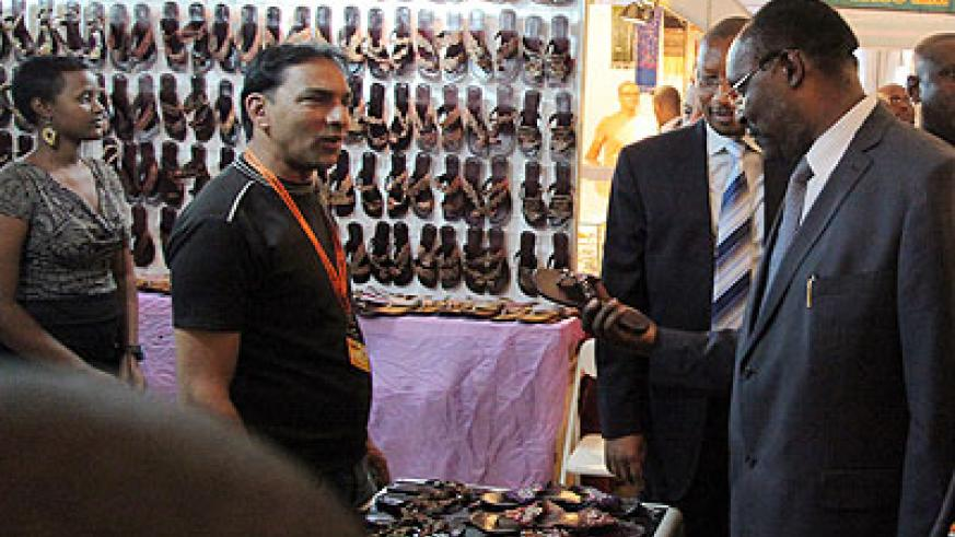 Trade and Industry Minister Francois Kanimba (R) with BNR Governor John Rwangombwa look at shoes on one of the stands at the Expo yesterday. John Mbanda