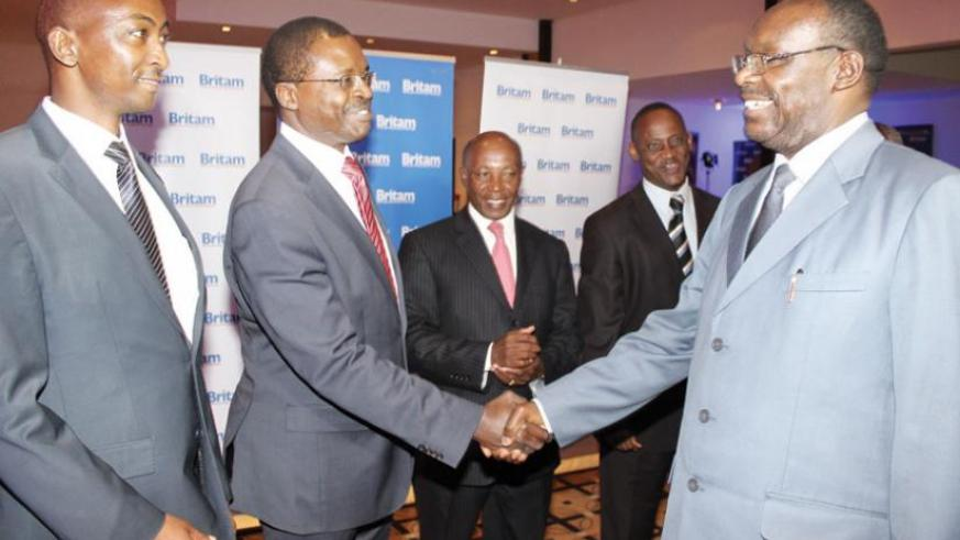 Britam's Stephen Wandera (centre) greets trade Minister Francois Kanimba (right) at the launch as Britam Rwanda general manager Reuben Kibiru (left) and other officials look on. (Ben Gasore)