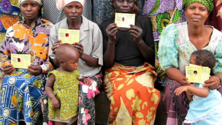 Mothers  pose in a group photo with their Mutuelle de Sante cards. File.
