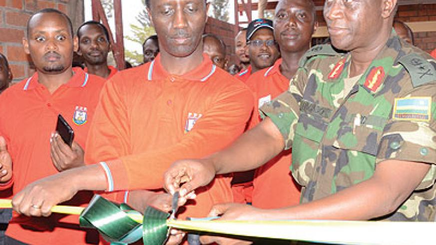 Kanyankole and Bagabo (R) cut the tape to launch the newly restocked veterans shop in Rusheshe village.