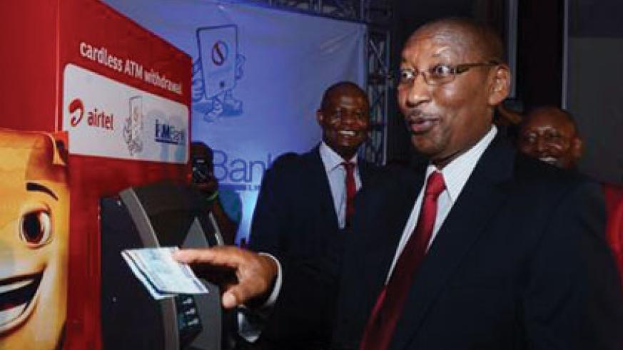 Central bank chief John Rwangombwa withdraws money from an I&M Bank ATM to launch an Airtel Money and I&M Bank partnership that enabled Airtel Money clients to withdraw cash from the bank's ATMs. (File)