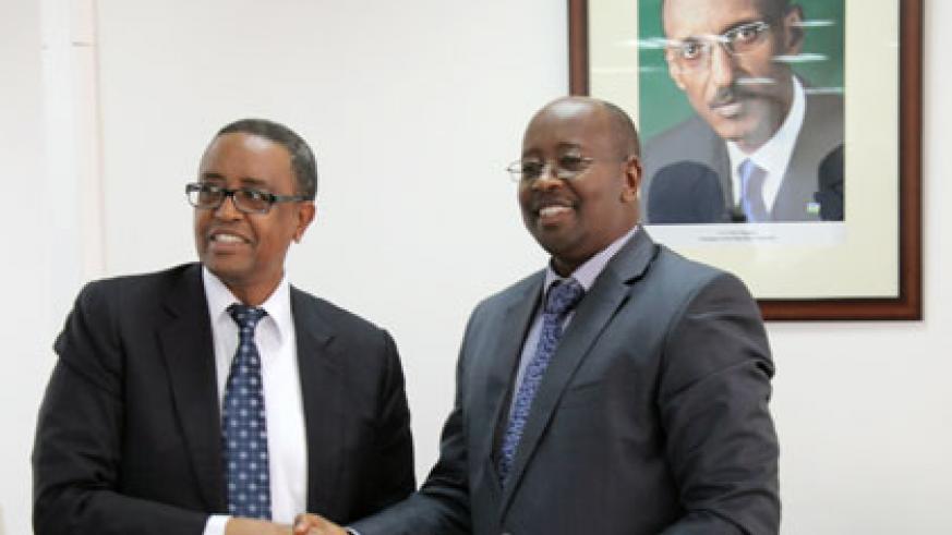 Former Infrastructure Minister Prof. Silas Lwakabamba (L) hands over to his successor Minister James Musoni yesterday. Lwakabamba is the new education minister. (John Mbanda)