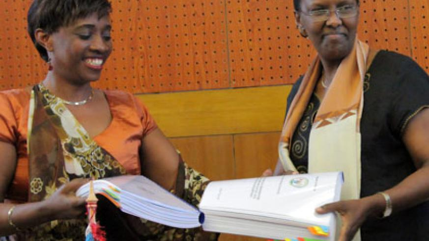 Rugwabiza (right) receives documents from her predecessor Muhongayire, at the handover yesterday. (John Mbanda)