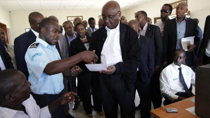 An Immigration Officer at Nemba Border post (L) chats with African Development Bank President Donald Kaberuka (R) in the recent past. (File)