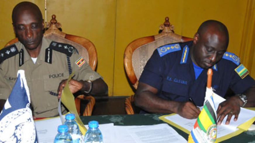 Uganda's Inspector General of Police Kale Kayihura (L), and his Rwandan counterpart Emmanuel. K. Gasana ink a deal during the meeting in the Ugandan South Western town of Kabale yesterday. Courtesy .