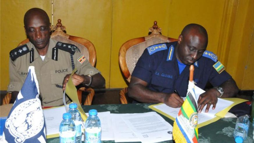 Uganda's Inspector General of Police Kale Kayihura (L), and his Rwandan counterpart Emmanuel. K. Gasana ink a deal during the meeting in the Ugandan South Western town of Kabale yesterday. (Courtesy)