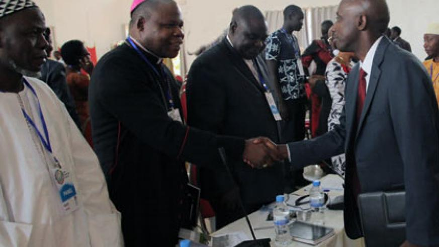 Local Government minister Francis Kaboneka (R) greets Archbishop Dieudonné Nzapalainga of Bangui, Central African Republic, at the opening of the Global Peacebuilders Conference in Kigali yesterday. (John Mbanda)