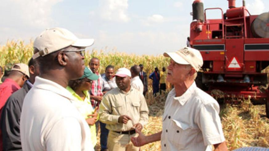 Premier Anastase Murekezi listens to irrigation specialist Keith McGaw explain how a combine harvestor operates. (Stephen Rwembeho)