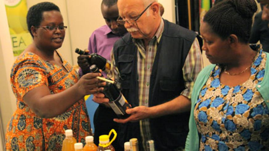 Christine Murebwayire (L), a local exporter, explains about her banana wine at the National Exporters' Forum in Kigali yesterday. (John Mbanda)