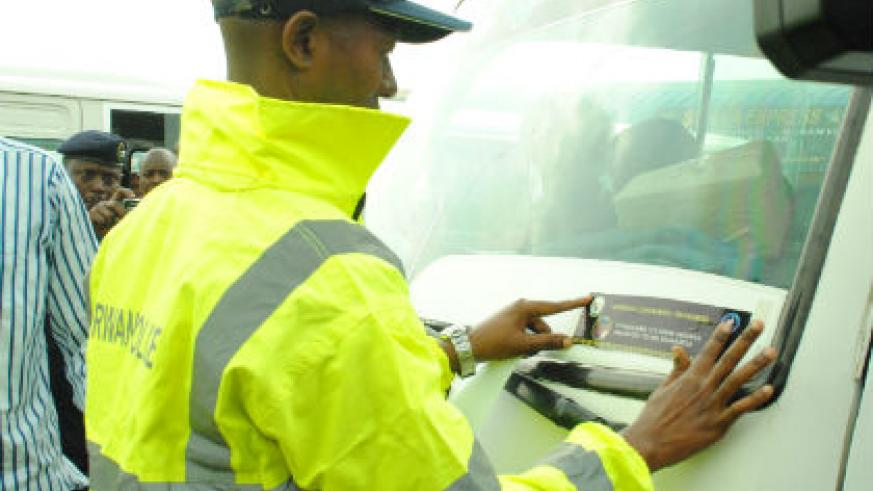 Minister Musa Fazil Harelimana puts a sticker on a vehicle during the launch of Road Safety Campaign in Kigali on Wednesday. (Courtesy)