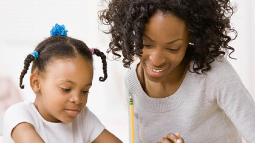 A parent helps her daughter with homework. Experts encourage parents to guide their children but avoid doing homework for them. (Internet photo)