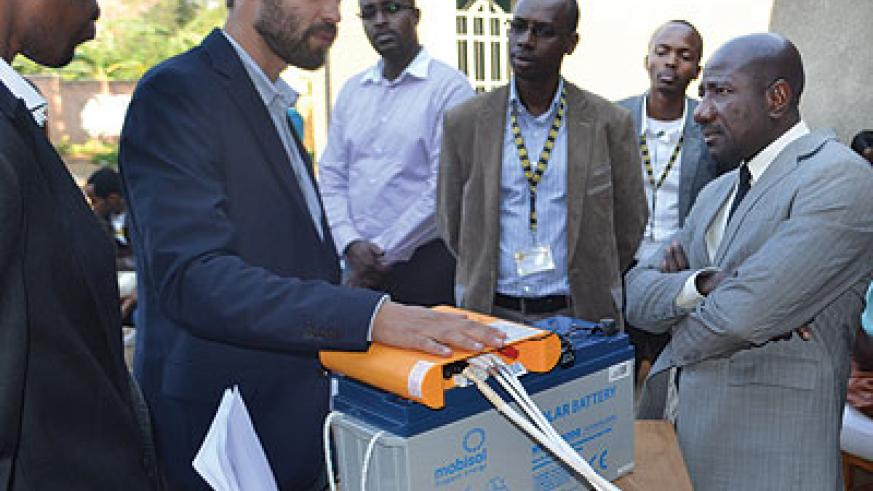 Mobisol's Maier (left) explains how the solar unit works as MTN boss Asante (right) and other officials look on. The firm celebrated its 1,000th installation on Wednesday. Michel Nkurunziza.