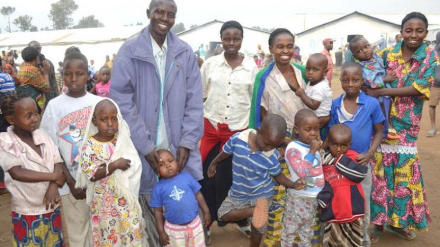 Singirankabo poses for a photo with his two wives and children repatriated last year. (Jean Pierre Bucyensenge)