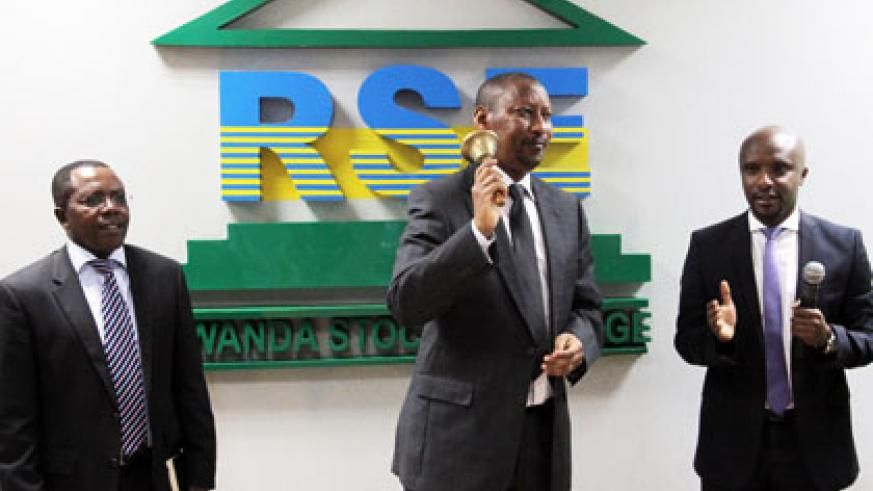Central bank governor John Rwagombwa (C) rings the bell to launch of the trading of the bonds yesterday as executive director CMA Robert Mathu (L) and RSE chief executive Celestin Rwabukumba look on. (John Mbanda)