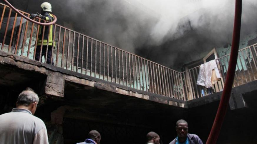 People remove property from the Muhima building as firefighters battle the raging fires yesterday. (John Mbanda)