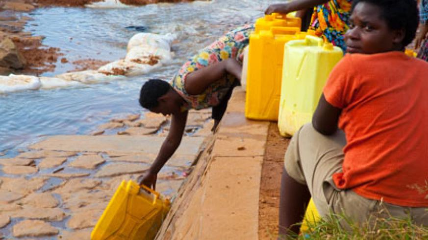 People draw water in Kimisagara, a Kigali city suburb.  Recent research shows that about  480 million people in Africa will face water scarcity by 2025. File.