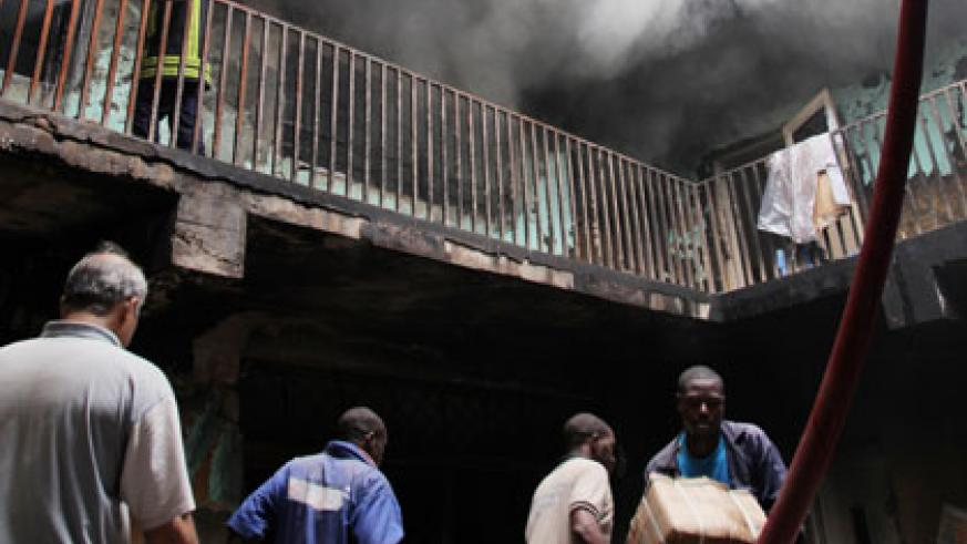 People remove property from the Muhima building as firefighters (top) battle the raging fires yesterday. John Mbanda.