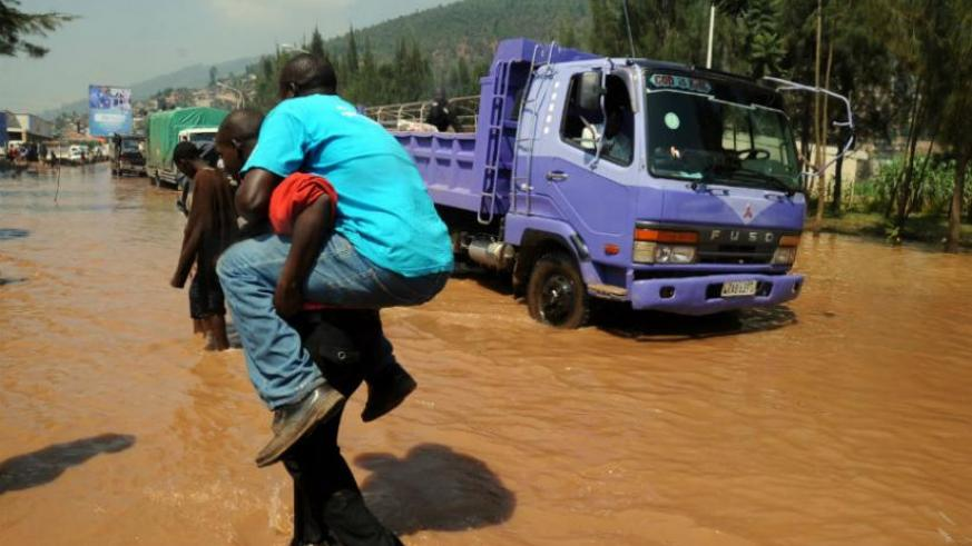 Torrential rainfall will result from global warming. A man is carried across the flooded Nyabugogo highway after paying 100 francs. (File)