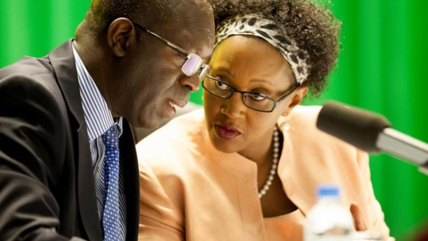 Prime Minister Anastase Murekezi chats with Stella Ford Mugabo, the minister for Cabinet affairs, during the Imihigo validation meeting at the Office of the Prime Minister yesterday. (Timothy Kisambira)