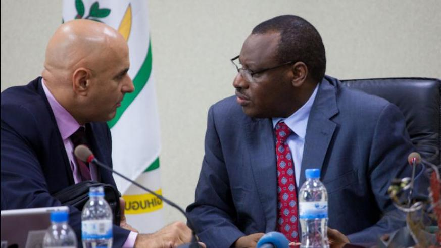 Drummond (L) chats with Amb.  Gatete at the media briefing in Kigali yesterday.(Timothy Kisambira)