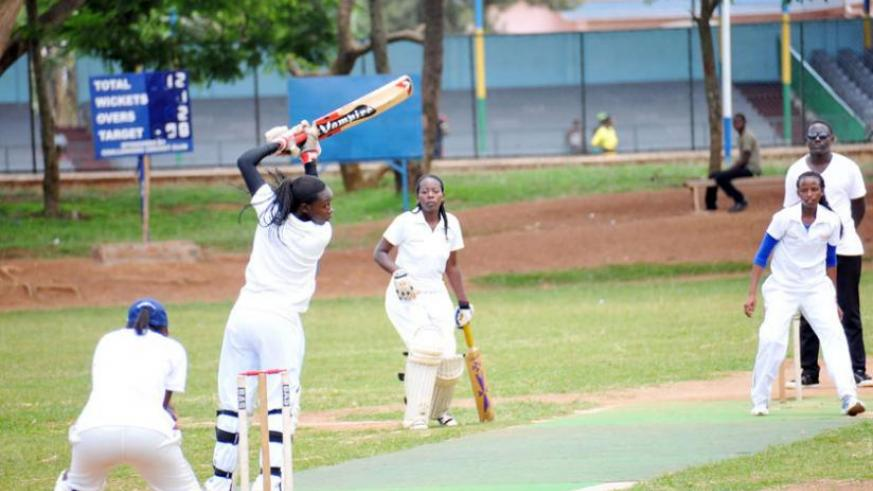 Queens of Victory captain Jeanne d'Arc Sibo (L) takes a shot off the bowling of Betty Mukunzi (R) of White Clouds CC. (Pontian Kabeera)