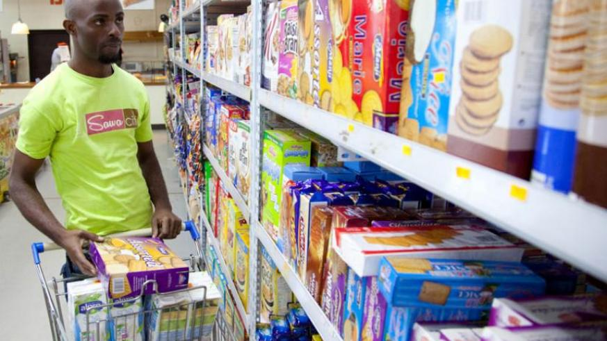 A sworker stocks biscuits at a city supermarket. WHO seeks to regulate advertising of  such foods. (Courtesy)