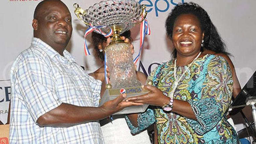 Kashaka, left, receives the overall winners trophy from Uganda's state minister for fisheries Ruth Nankabirwa. (Courtesy photo)