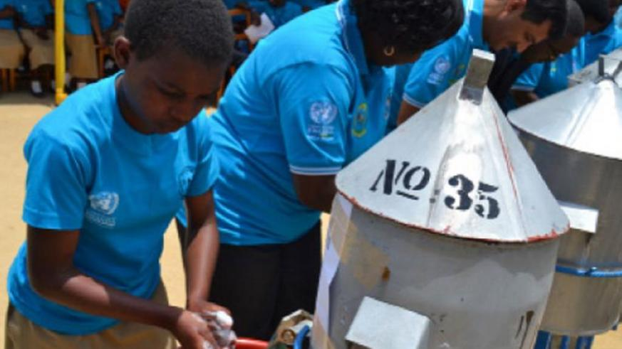 A secondary school student joins officials in washing hands in Nyabihu. Officials urged Rwandans to join efforts to promote hygiene. (Jean d'Amour Mbonyinshuti)