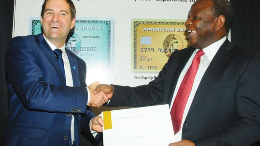 Andrew Stewart, the Partner Card Services Turkey, Middle East and Africa vice-president (left), shares a light moment with Equity Bank Group chief executive officer, James Mwangi, after signing the agreement in Kenya this week. (Net photo)