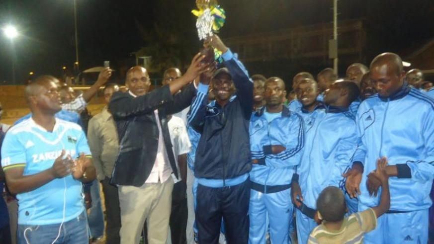 Police Coach Antoine Ntabanganyimana hoists one of the 4 trophies that they won this year. (Pontina Kabeera)