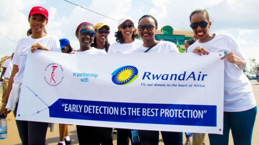 A group of women hold a RwandAir banner during a march in Kigali to raise awareness about breast cancer.(Timothy Kisambira)