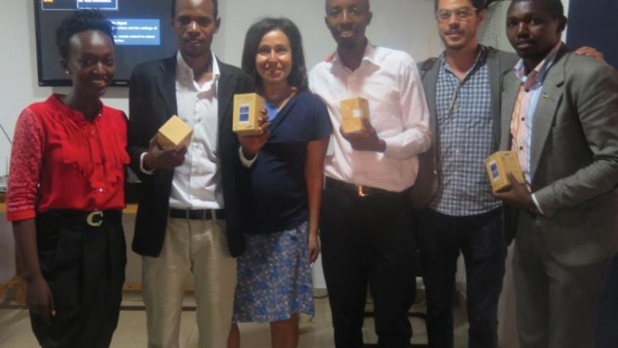 Smart business' Rubagumya (second left) and the other winners display mobile phones they got as part of the winners' package. (Solomon Asaba)
