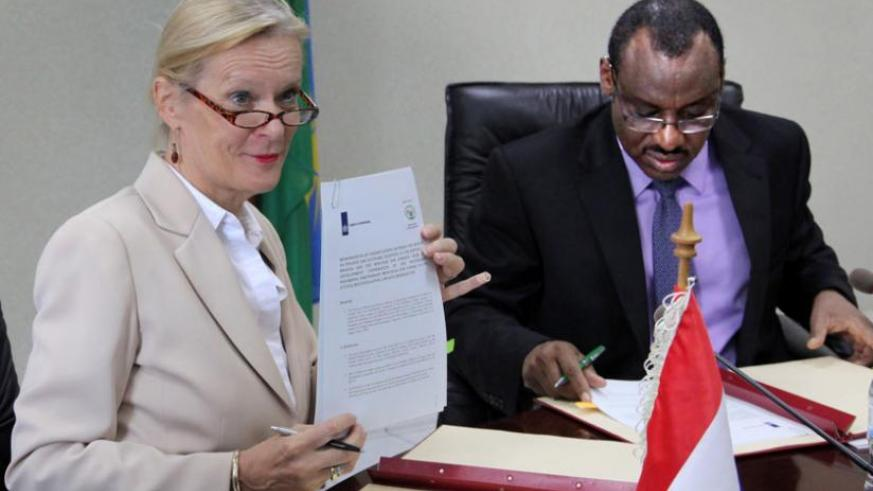 Amb. Leoni Cuelenaere of the Kingdom of Netherlands (L) shows a copy of the memorandum of understanding as Finance minister Claver Gatete signs his copy yesterday. (John Mbanda)