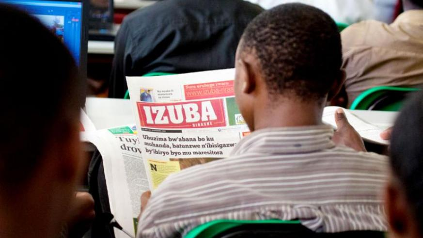 A journalism student at University of Rwanda's School of Arts and Social Sciences reads  Izuba, a Kinyarwanda newspaper. The method of representing the sounds of the local dialect by written or printedsymbols have been revised. (Timothy Kisambira)